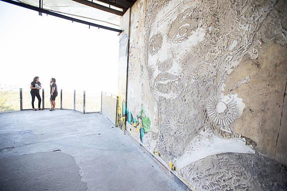 """Monica Benicio, Marielle Francos Partnerin, und der Künstler Vhils in der Nähe des Wandbildes """"Brave Wall"""" zu Ehren von Marielle Franco in Lissabon, Portugal, September 2018 © Fernando Figueiredo Silva"""